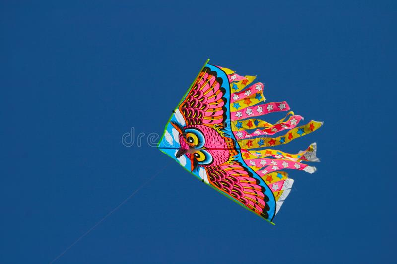 A bright kite against a blue sky without clouds. royalty free stock photography
