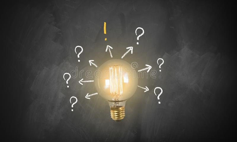 Bright lamp with arrows in different directions and one pointing to a solution. Bright lamp on blackboard with arrows in different directions and one pointing to stock photography