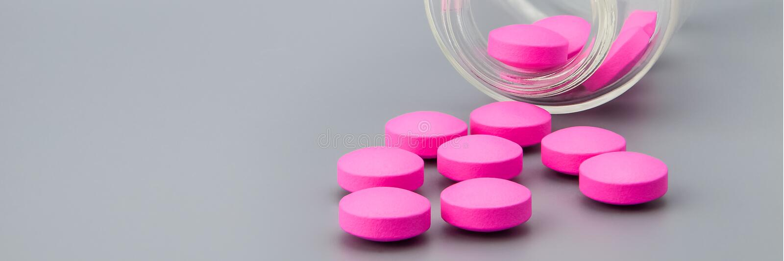 Bright large pink pills are poured from a glass jar on a gray background. stock photography