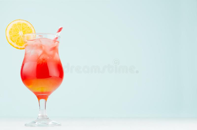 Bright layered red, yellow alcohol cocktail with oranges slice, straw, ice in elegant wineglass on soft light pastel blue. royalty free stock images