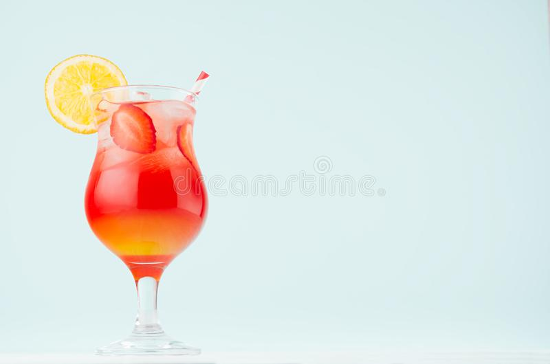 Bright layered red, yellow alcohol cocktail with oranges slice, straw, ice, strawberry in wineglass on soft light pastel blue. royalty free stock photos
