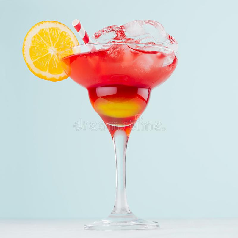 Bright layered red and yellow alcohol cocktail with oranges slice, straw, ice in wineglass on soft light pastel blue background. stock photos