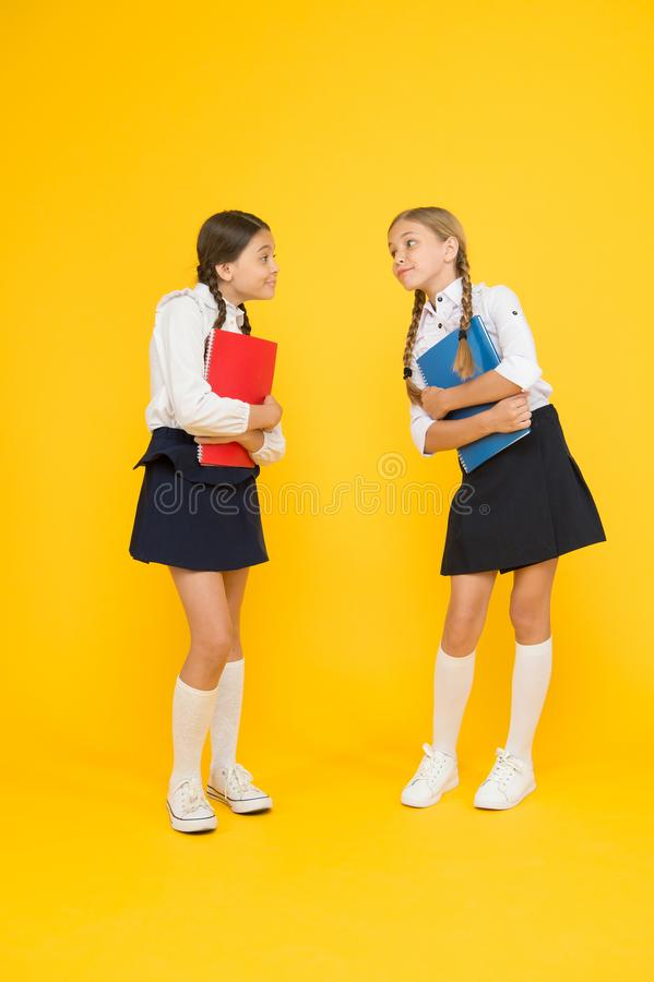 Bright life. cheerful classmates with workbook. little girls in school uniform. dictionary notebook. Get information. Reading story. childrens literature. kids stock photos