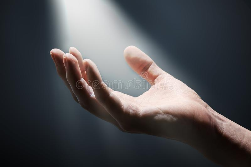 Bright light rays shihing on man`s hand in darkness. stock image