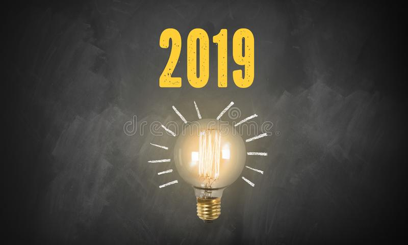 Lightbulb on a blackboard and the number 2019. Bright lightbulb on a blackboard and the number 2019 stock image