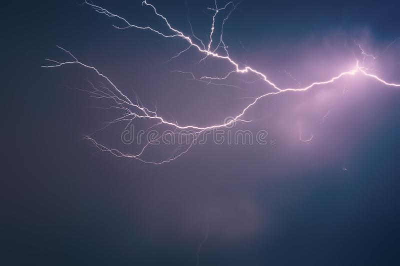 Bright lightning against background of dramatic night sky with clouds, discharged atmospheric electricity in air stock images