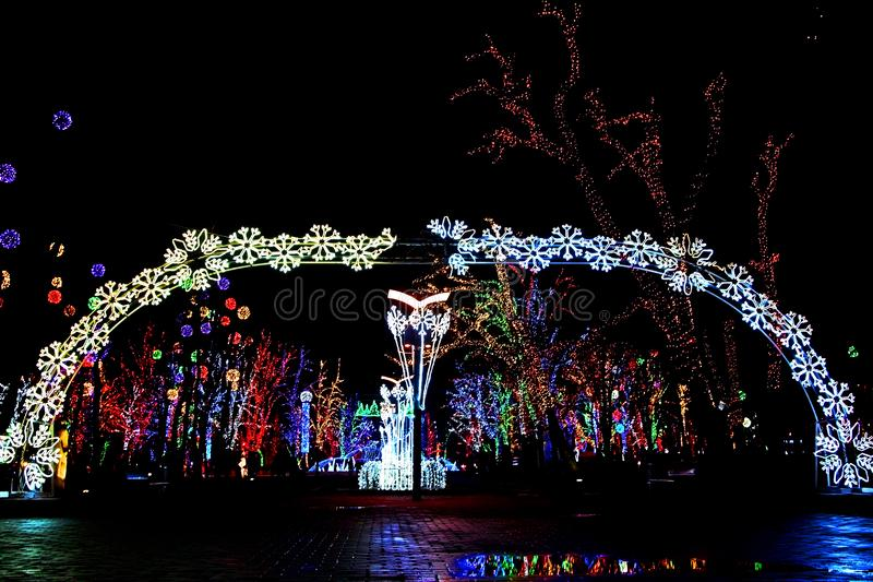 Bright lights arch at the entrance to park globa of Dnipro city in Ukraine. hanging garlands and festive decorations of the night. City for the New Year stock photography