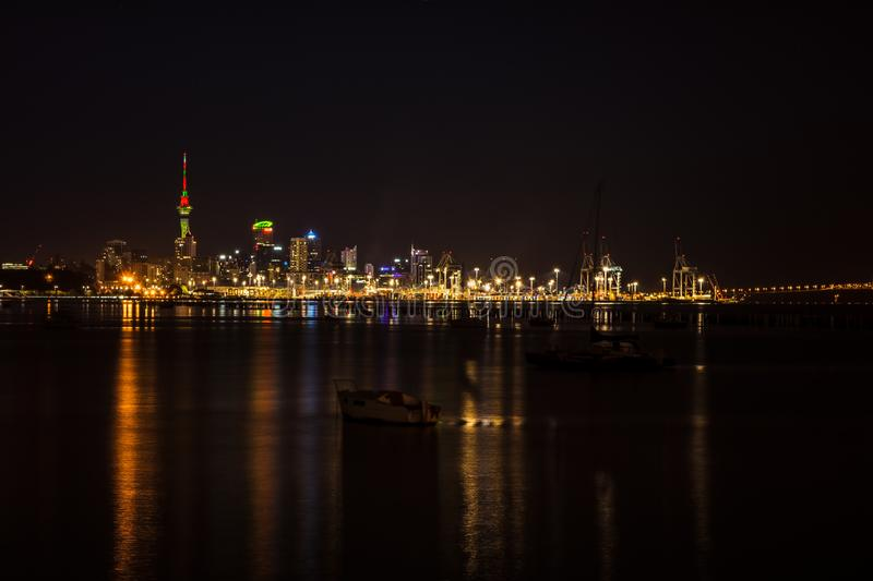 Bright lights of Auckland city downtown and the port reflected in Okahu bay with a small boat in the foreground. Soft royalty free stock images