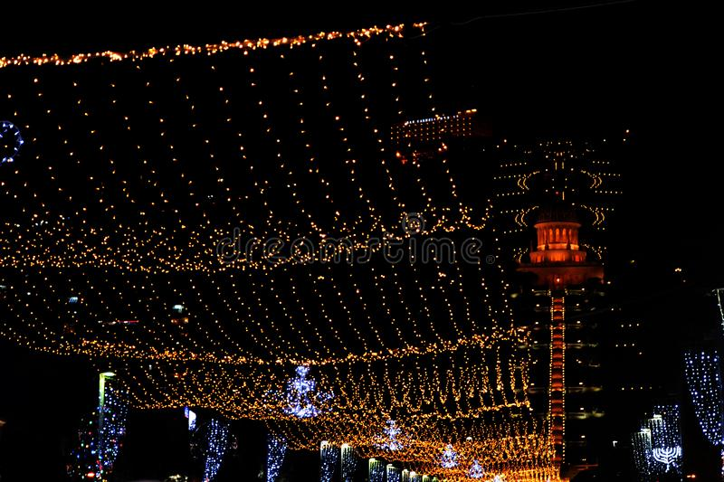 Bright lights on Ben Gurion street of Haifa city in Israel, view of the Bahai temple. hanging garlands and festive decorations. Of the night city for the New stock photography