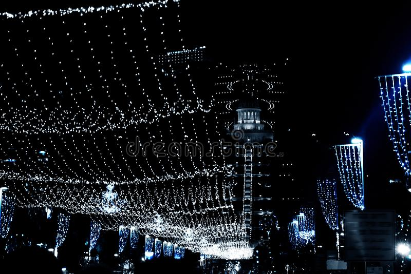 Bright lights on Ben Gurion street of Haifa city in Israel, view of the Bahai temple. hanging garlands and festive decorations. Of the night city for the New royalty free stock photography