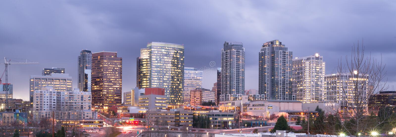 Bright Lights City Skyline Downtown Bellevue Washington USA. A clear panoramic view of Bellevue, WA with a storm passing at dusk stock photo