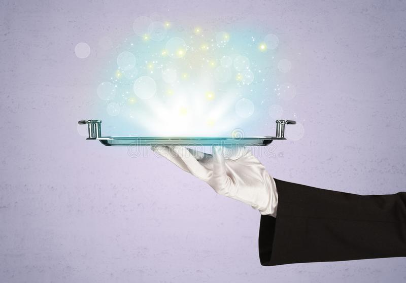 Bright lights presented on tray by waiter. Glowing lights glitter on silver plate served on tray by waiter hand in white elegant glove in front of purple stock image