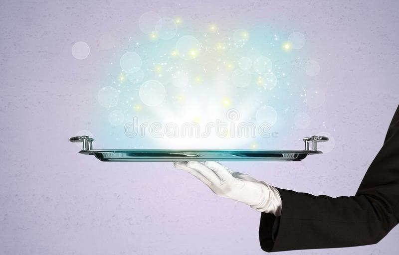 Bright lights presented on tray by waiter. Glowing lights glitter on silver plate served on tray by waiter hand in white elegant glove in front of purple royalty free stock image
