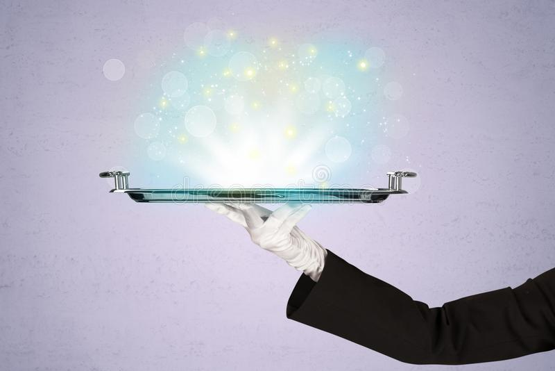Bright lights presented on tray by waiter. Glowing lights glitter on silver plate served on tray by waiter hand in white elegant glove in front of purple royalty free stock photos