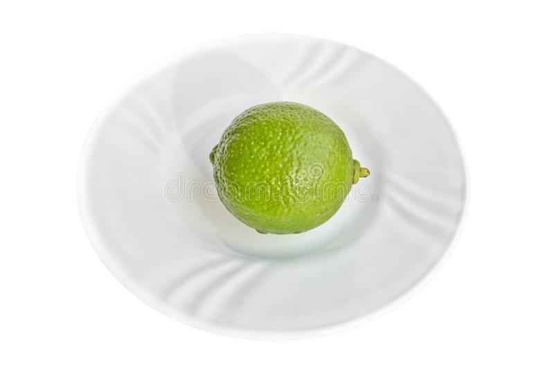 Bright lime green on white porcelain plate isolated on white background royalty free stock images