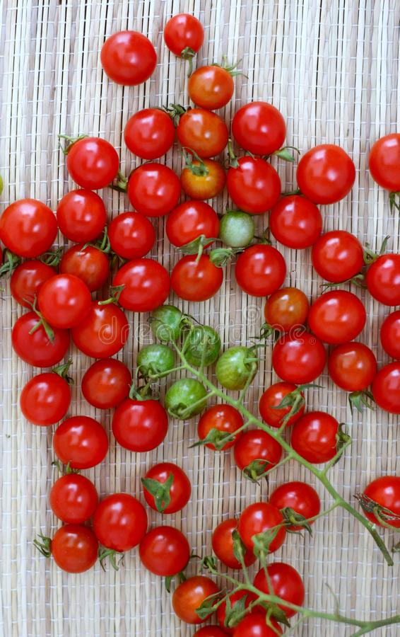 Small red and green cherry tomatoes lie on a bamboo napkin stock image