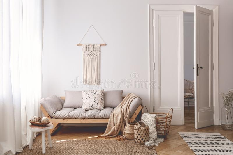 Bright living room interior with unique, handmade baskets made of natural materials and a cozy wooden sofa with beige cushions. Concept stock image