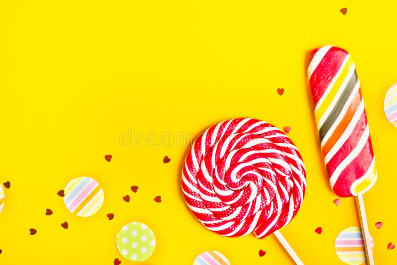 Bright lollipops with multi-colored candy on yellow royalty free stock image
