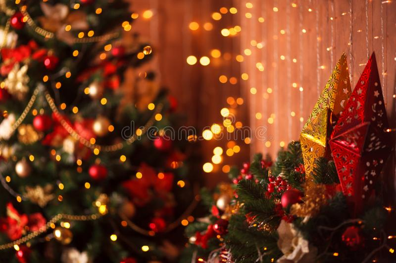 Christmas tree blurred background witn stars and luminosity. Bright and luminosity blurred background with Christmas tree. Holiday design with yellow and red royalty free stock photography
