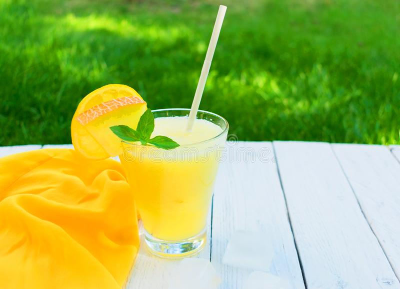 Bright melon smoothie with mint and lemon on a background of fresh green grass. Copy space. Concept of summer cooling drinks. Bright smoothie made from melon royalty free stock photos