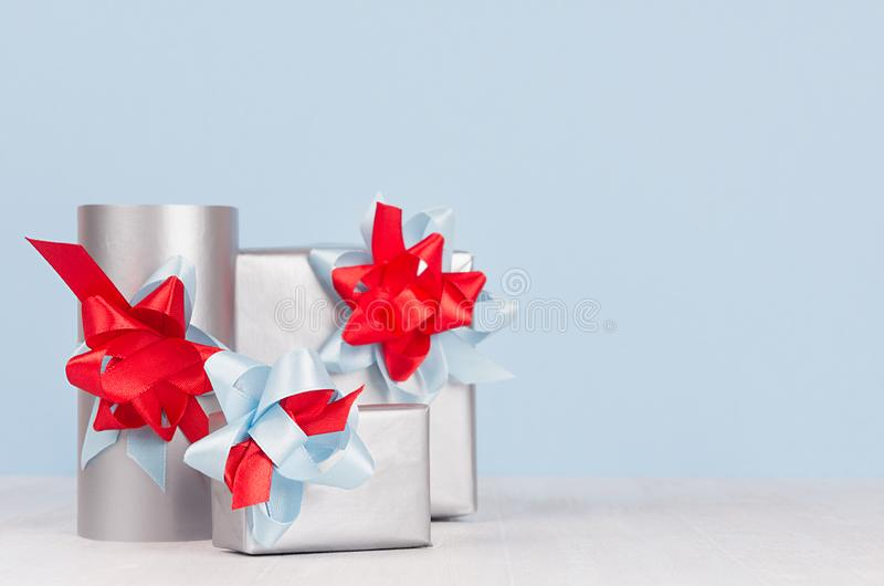 Bright metallic paper gift boxes with red and blue satin ribbons and bows on soft light white wood board. royalty free stock photo