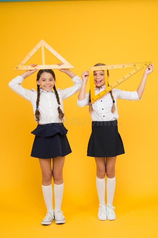 Bright minds. Kids in uniform at yellow wall. friendship and sisterhood. happy small girls study mathematics. students. Use gon ruler. stem disciplines. back to stock photos