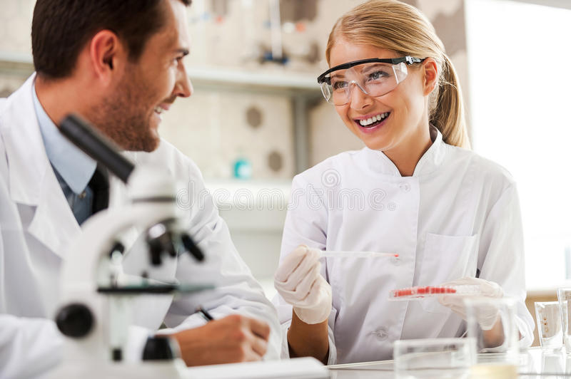 Bright minds at work. Two cheerful young scientists making experiments and looking at each other while sitting in the laboratory royalty free stock image