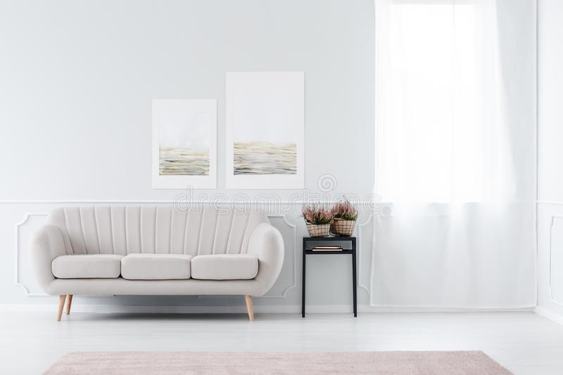 Beige sofa near window. Bright, minimalist living room interior with beige sofa standing near the window and black stool royalty free stock photography