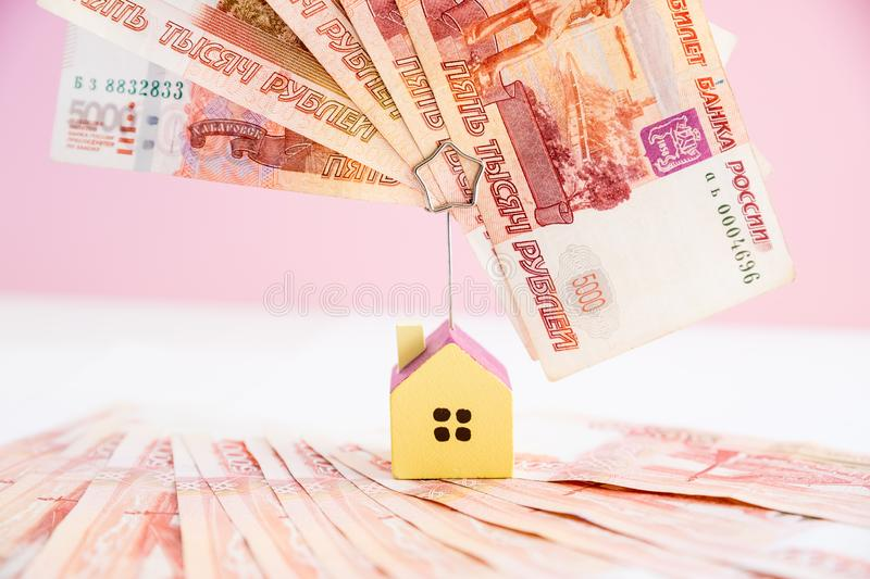 Model of the house standing on five thousand banknotes.Rental estate.Sale property template.Model of wooden house with royalty free stock image