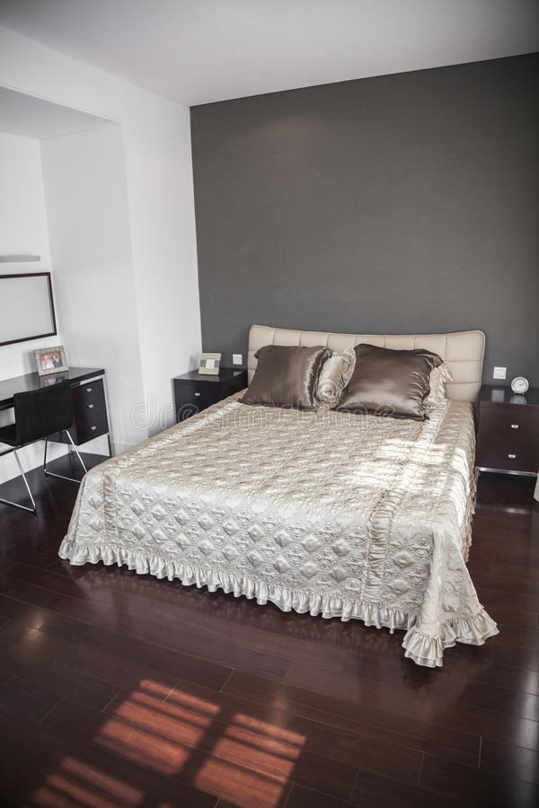 Bright, modern bedroom with beige bedspread. stock photography