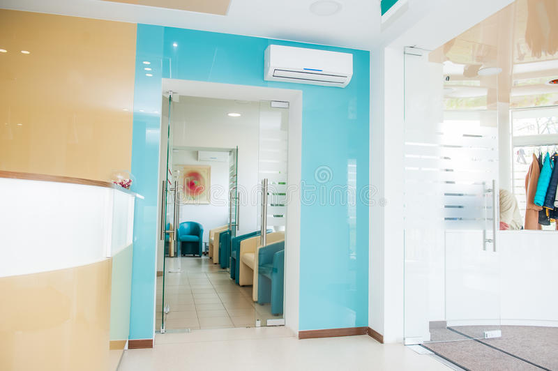 Bright modern interior of waiting hall with reception and wardrobe zones. Selective focus stock photo