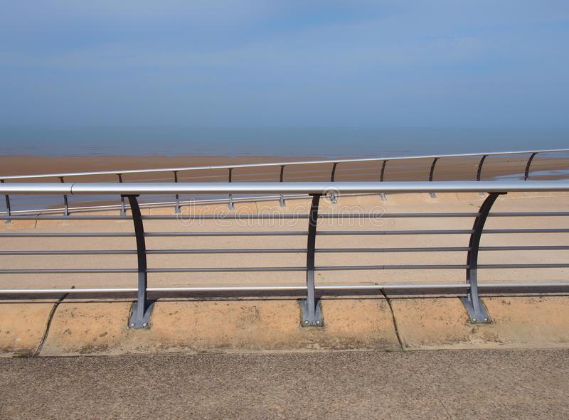 Bright modern metal railings along the seaside promenade in blackpool lancashire with concrete sea wall with ocean and blue sky royalty free stock photo