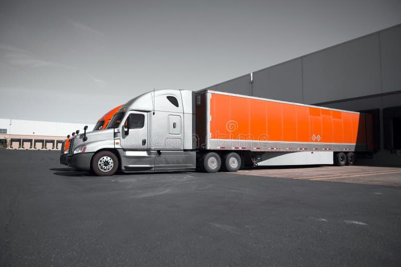 Bright modern orange and gray semi trucks unloading in warehouse stock photography