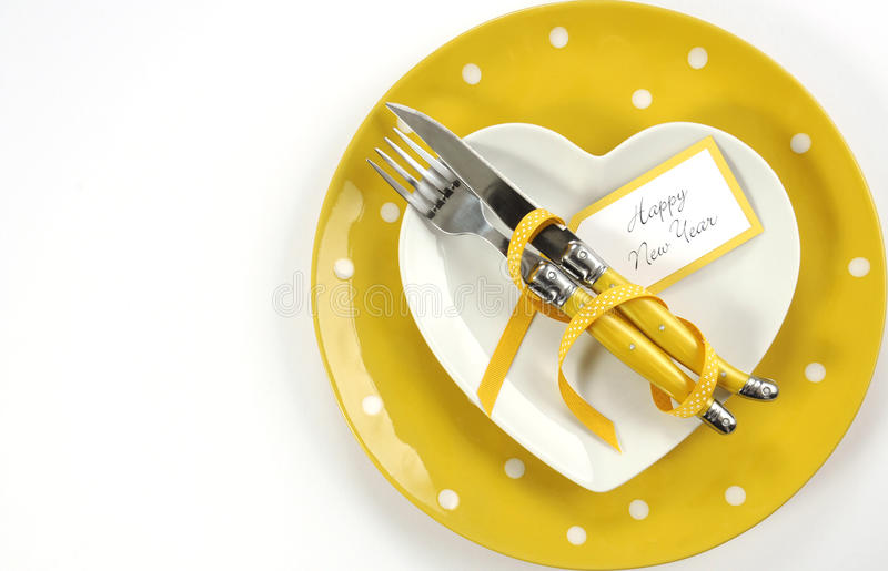 Bright and modern yellow and white theme Happy New Year table. With heart shape plate on polka dot place setting, with copy space stock photo