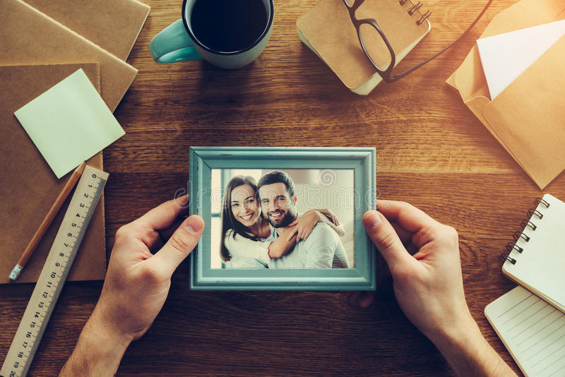 Bright moments together. Close-up top view of men holding photograph of young couple over wooden desk with different chancellery stuff laying around royalty free stock photography