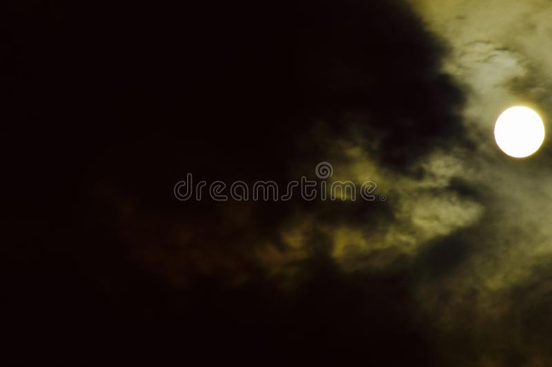 The bright moon shining through the clouds. A near full moon embedded in the clouds brightens the night sky stock image