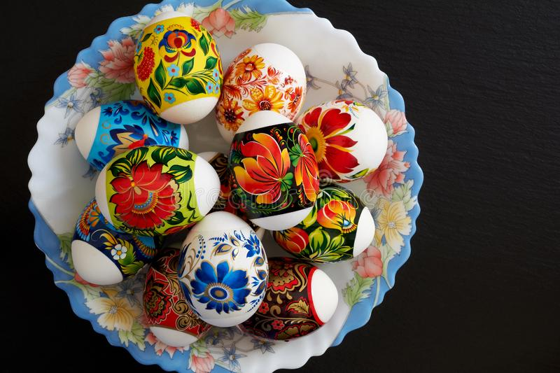 Bright multi-colored Easter eggs with floral pattern in plate on dark background. Symbol of religious holiday royalty free stock images