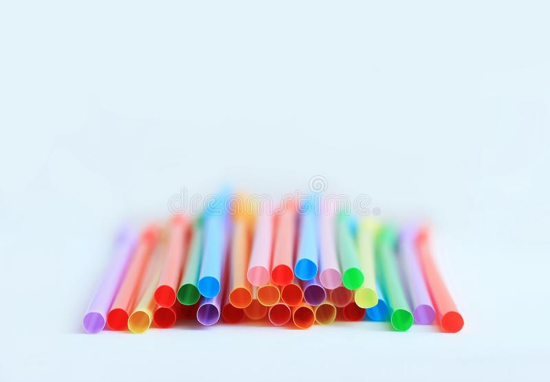 Bright multi-colored plastic tubules on a white background, place for text stock photography