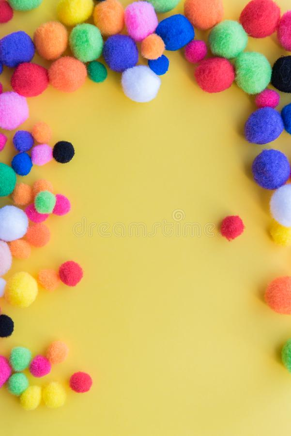 Bright multi-colored pom-poms arranged as a border on a solid yellow background royalty free stock image