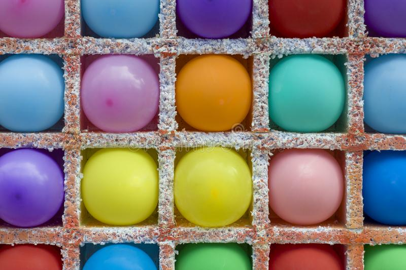 Bright multi-colored round balloons in square niches from styrofoam close up in a dash. rough surface texture. A bright multi-colored round balloons in square royalty free stock photo