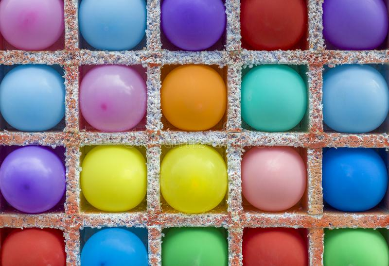 Bright multi-colored round balloons in square niches from styrofoam in a dash. rough surface texture. A bright multi-colored round balloons in square niches from stock photo