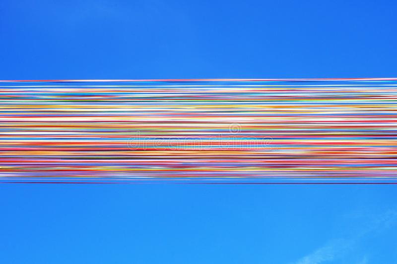 Bright multi-colored satin ribbons develop against the blue sky. Multi-colored line. Ostend, Belgium royalty free stock photo