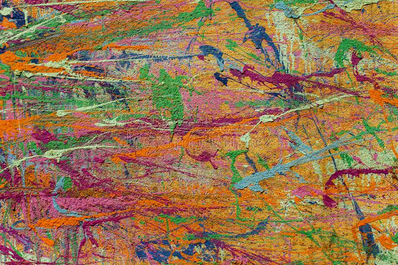 Bright multi-colored spots and splashes of paint on a concrete wall stock image