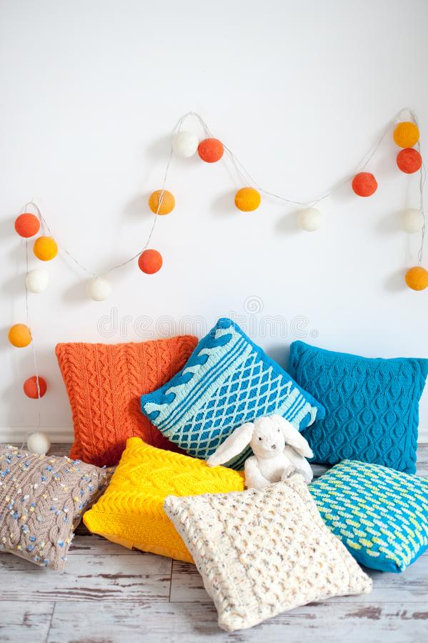 Bright multicolored knitted cushions stock photo