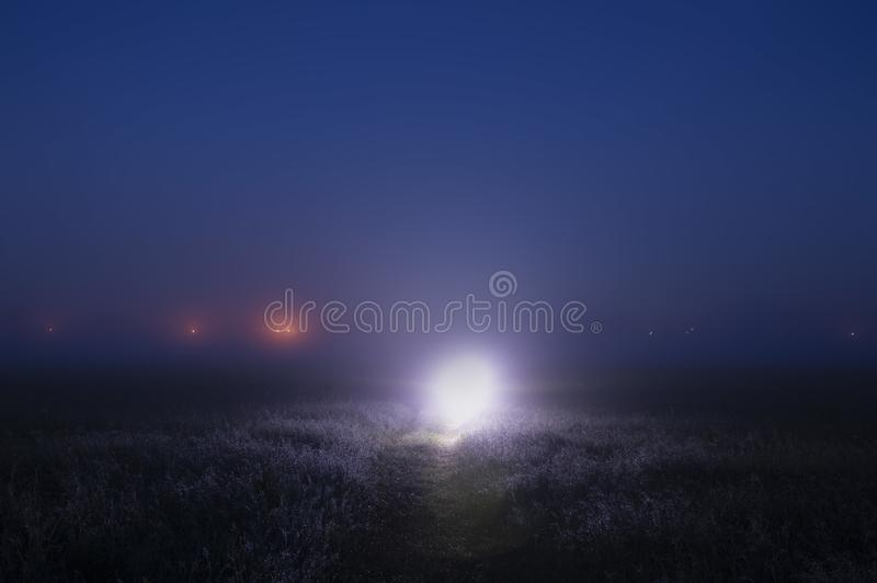 A bright mysterious light on a path on a misty night, with glowing lights on the horizon stock photography