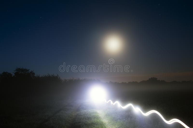 A bright mysterious light trail on a country path on a misty night, with glowing moon in the night sky stock image