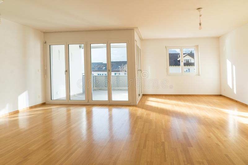 Bright new living room in an empty apartment with french doors and parquet wooden floors royalty free stock image