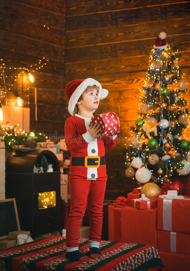 Bright New Years interior. Boy cute child cheerful mood play near Christmas tree. Indoor. Joy and happiness. Christmas stock photo