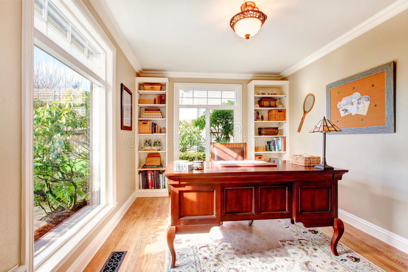 Bright office room with classic desk and built-in shelves stock photography