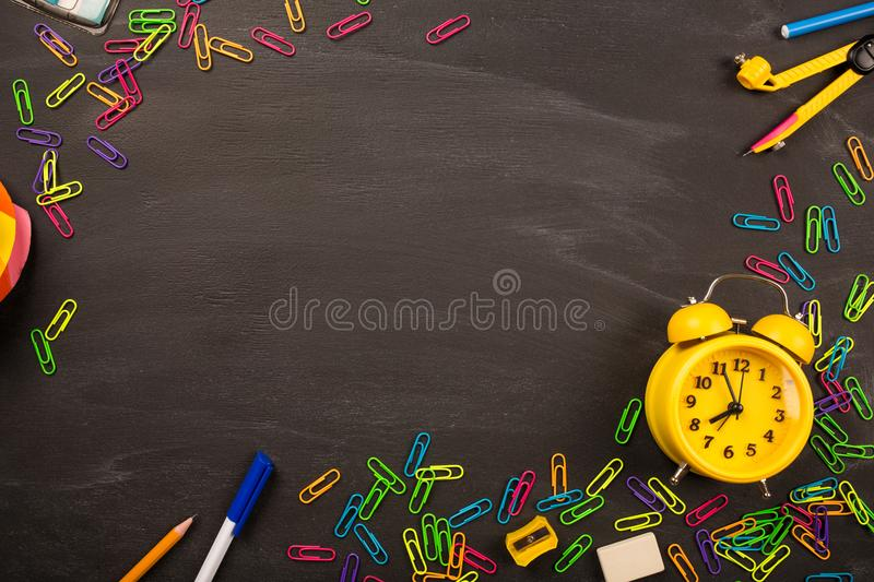 Bright office supplies, yellow alarm clock on black chalkboard top view, copy space. concept: back to school royalty free stock photography